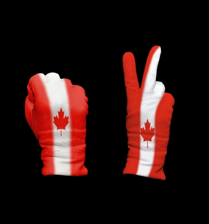 Clenched fist in leather glove, and hand with victory gesture in a glove decorated with Canada flag photo