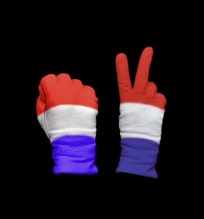 Clenched fist in leather glove, and hand with victory gesture in a glove decorated with Netherlands flag photo