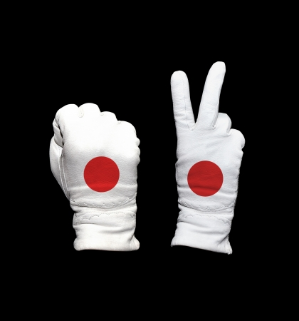 Clenched fist in leather glove, and hand with victory gesture in a glove decorated with Japan flag photo