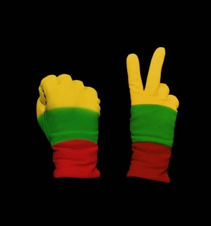 Clenched fist in leather glove, and hand with victory gesture in a glove decorated with  Lithuania flag photo
