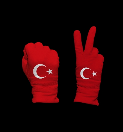 foreign policy: Clenched fist in leather glove, and hand with victory gesture in a glove decorated with Turkey flag