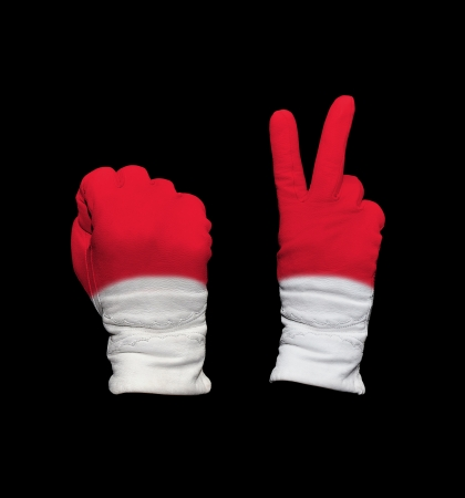 Clenched fist in leather glove, and hand with victory gesture in a glove decorated with Indonesia flag photo