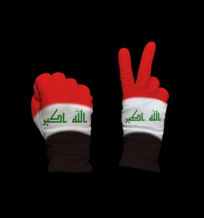 Clenched fist in leather glove, and hand with victory gesture in a glove decorated with Iraq flag photo