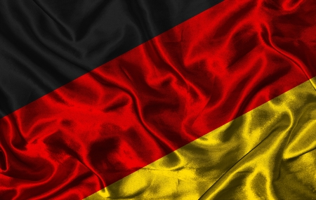 Waving colorful German flag on a silk background photo