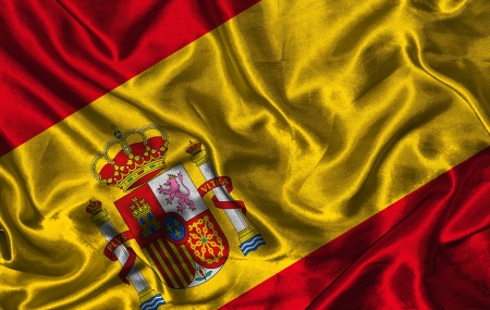 colorific: Waving colorful Spanish flag on a silk background Stock Photo