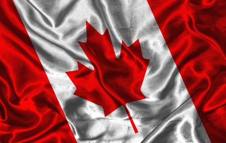 Waving colorful Canadian flag on a silk background photo