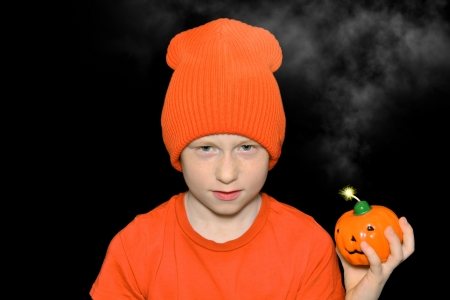 Boy in orange holds burning fuse pumpkin bomb photo
