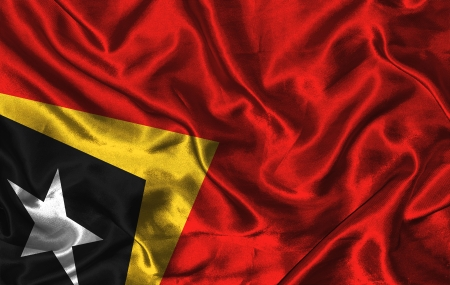 timor: Waving colorful East Timor flag on a silk background Stock Photo