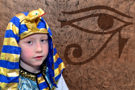 Portrait of a boy pharao on a stoned wall background photo