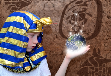 symbolism: Portrait of a boy pharao on a stoned wall background Stock Photo