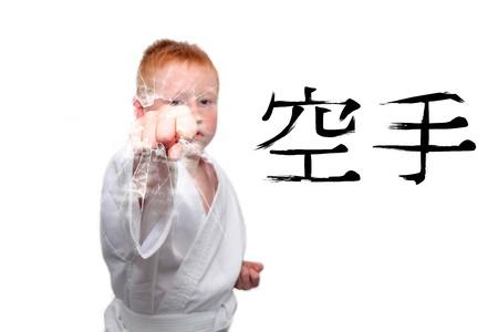 agression: Boy in white kimono showing a fight kick Stock Photo