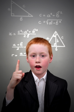 Young red-haired boy stands near the blackboard with formulas photo
