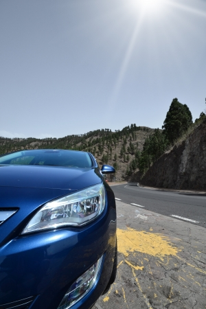 Blue car on a winding mountain road background photo