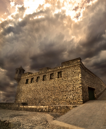 thicken: Medieval fortress under golden dramatic skies