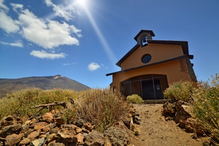 Old chapel under sun beam on a high mountain background photo