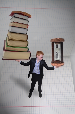 Schoolboy holding pile of books in one hand and sundial in other photo