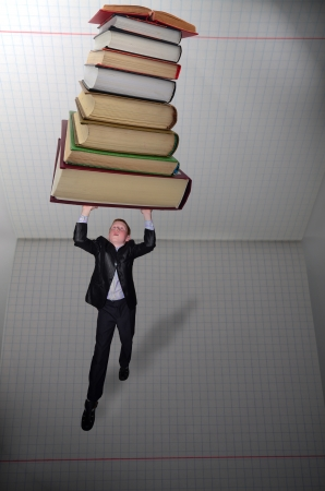 Schoolboy holding pile of books above his head photo