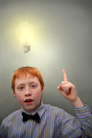 Young redhead boy with shining light bulb over his head photo