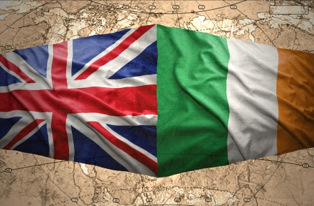 irish map: Waving British and Irish flags on the background of the political map of the world