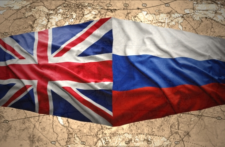 Waving British and Russian flags on the background of the political map of the world photo