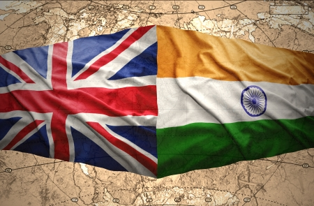 Waving British and Indian flags on the background of the political map of the world