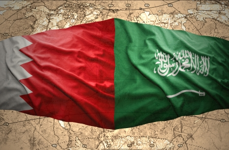 Waving Saudi Arabia and Bahraini flags on the background of the political map of the world photo