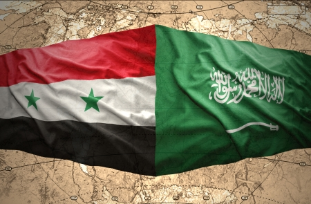 Waving Saudi Arabia and Syrian flags on the background of the political map of the world photo