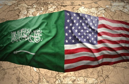 Waving Saudi Arabia and United States of America flags on the background of the political map of the world photo