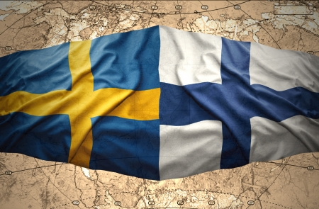 Waving Finnish and Swedish flags on the background of the political map of the world photo