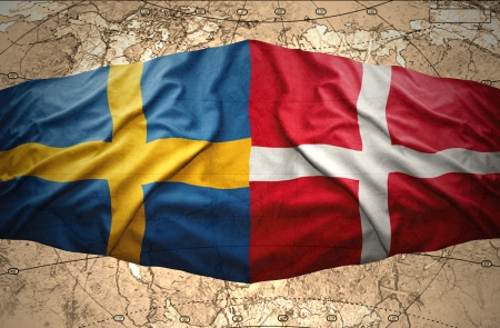 Waving Danish and Swedish flags on the background of the political map of the world photo