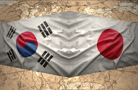 Waving Japanese and South Korea flags on the background of the political map of the world