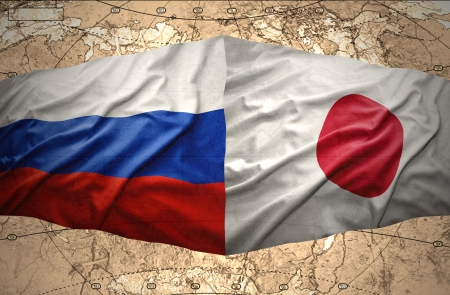 Waving Japanese and Russian flags on the background of the political map of the world photo