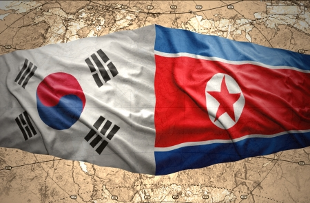 Waving North Korea and South Korea flags on the background of the political map of the world photo