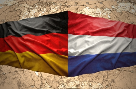 east berlin: Waving Dutch and German flags on the background of the political map of the world Stock Photo