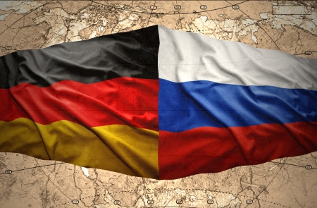 Waving Russian and German flags on the background of the political map of the world Stock Photo