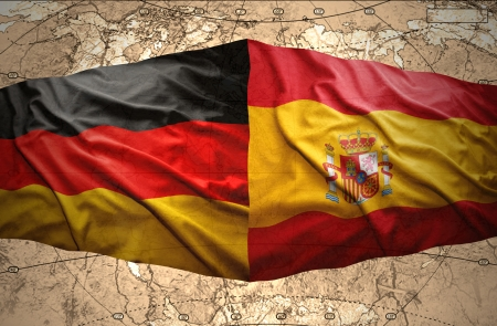 Waving Spanish and German flags on the background of the political map of the world photo
