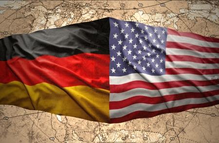 Wuivende Amerikaanse en Duitse vlaggen op de achtergrond van de politieke kaart van de wereld Stockfoto