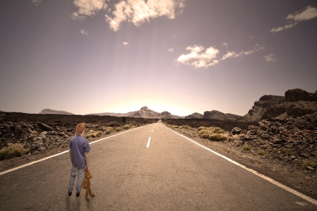 Boy standing on a lonely road with a teddy-bear in his hand photo
