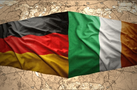 Waving Irish and German flags of the political map of the world photo