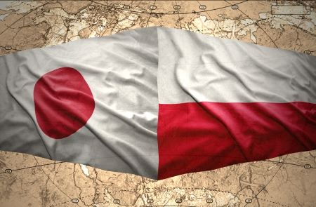 Waving Polish and Japanese flags of the political map of the world photo