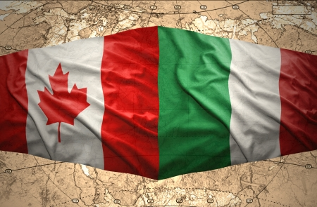 Waving Italian and Canadian flags of the political map