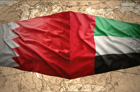 Waving United Arab Emirates and Bahraini flags on the of the political map of the world photo