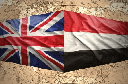 Waving Yemeni and British flags on the of the political map of the world photo