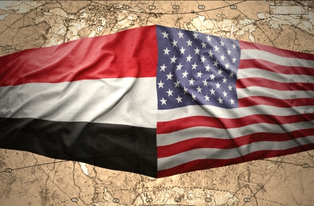 Waving Yemeni and American flags on the of the political map of the world photo