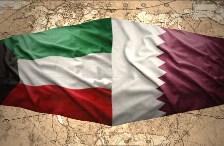 Waving Qatar and Kuwait flags on the of the political map of the world photo
