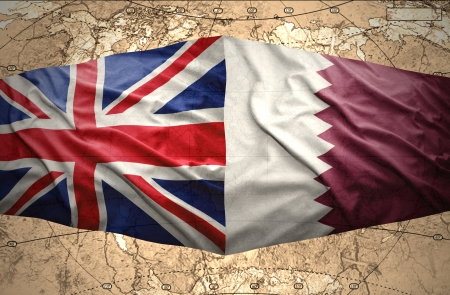 Waving Qatar and British flags on the of the political map of the world photo