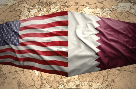 Waving Qatar and American flags on the of the political map of the world photo