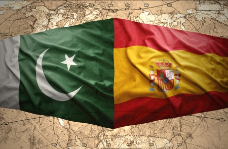 Waving Pakistani and Spanish flags on the of the political map of the world photo