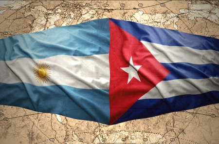 Waving Argentinean and Cuban flags on the background of the political map of the world photo