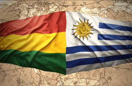 Waving Bolivian and Uruguayan flags on the of the political map of the world photo